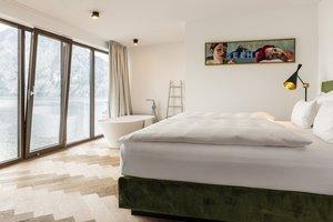 Schlafzimmer mit offenem Badezimmer und Blick auf den Traunstein